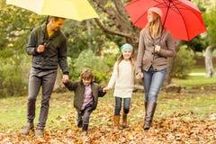 Familia joven sonriente debajo del paraguas Fotos de archivo libres de regalías