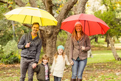 Familia joven sonriente debajo del paraguas Imagenes de archivo