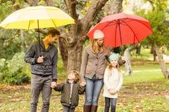 Familia joven sonriente debajo del paraguas Imágenes de archivo libres de regalías