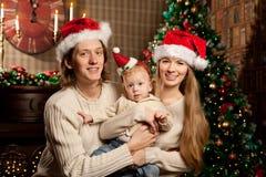 Familia joven sonriente feliz cerca del árbol de navidad Fotografía de archivo