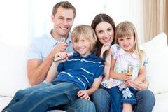 Familia joven sonriente que canta un Karaoke junto Imagen de archivo