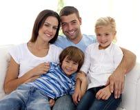 Familia joven sonriente que se sienta en el sofá Imagenes de archivo