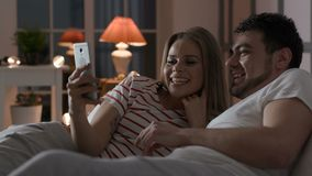 Familia joven usando el teléfono con Internet en dormitorio almacen de video