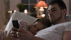 Familia joven usando el teléfono con Internet en dormitorio almacen de metraje de vídeo