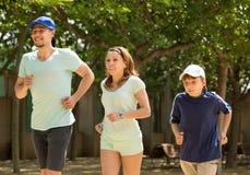 Familia juguetona con el hijo que corre en parque Fotografía de archivo libre de regalías