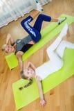 Familia juguetona de dos que tienen clase de aeróbicos en casa Imagen de archivo libre de regalías
