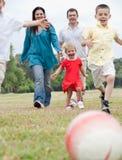 Familia juguetona que juega al balompié en el césped verde Imagenes de archivo
