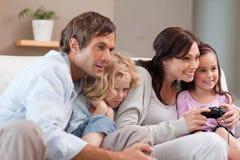 Familia juguetona que juega a los videojuegos juntos Foto de archivo libre de regalías