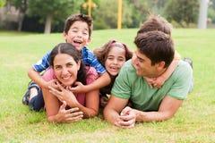 Familia juguetona que miente al aire libre y que sonríe Fotos de archivo libres de regalías