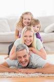 Familia juguetona que miente en uno a en sala de estar Foto de archivo libre de regalías