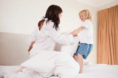 Familia juguetona que tiene lucha de almohada Foto de archivo libre de regalías