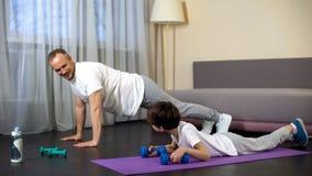 Familia juguetona seria que hace ejercicio del tablón con pesas de gimnasia en casa, modelo imagenes de archivo
