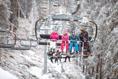 Familia junto en la silla del esquí que va a esquiar terreno Imagenes de archivo