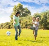 Familia junto que juega con el balón de fútbol Imagen de archivo