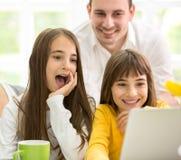 Familia junto que parece el ordenador portátil Imagen de archivo