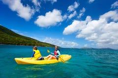 Familia kayaking en el océano tropical Foto de archivo