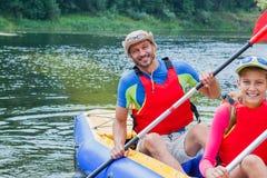 Familia kayaking en el río Foto de archivo