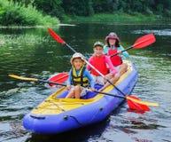 Familia kayaking en el río Imagen de archivo libre de regalías