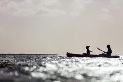 Familia kayaking en la puesta del sol imagen de archivo