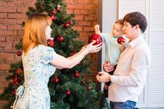 Familia, la Navidad, Navidad, invierno, felicidad y concepto de la gente - familia sonriente que adorna el árbol de navidad Foto de archivo libre de regalías