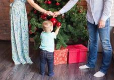 Familia, la Navidad, Navidad, invierno, felicidad y concepto de la gente - familia sonriente que adorna el árbol de navidad Imagen de archivo libre de regalías
