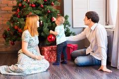 Familia, la Navidad, Navidad, invierno, felicidad y concepto de la gente - familia sonriente que adorna el árbol de navidad Imagen de archivo