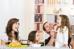 Familia linda con dos muchachas que comen el desayuno Foto de archivo