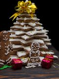 Familia linda del pan de jengibre cerca del árbol de navidad hecho en casa del pan de jengibre Imágenes de archivo libres de regalías