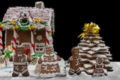 Familia linda del pan de jengibre cerca del pan de jengibre hecho en casa nevado h Foto de archivo