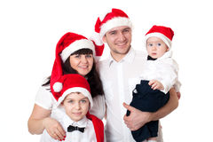 Familia linda feliz en los sombreros de santa imagen de archivo libre de regalías
