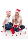 Familia linda feliz en los sombreros madre y niños de santa imagenes de archivo