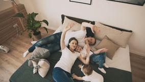 Familia linda que juega en cama en casa en dormitorio en la cámara lenta Visión superior almacen de metraje de vídeo