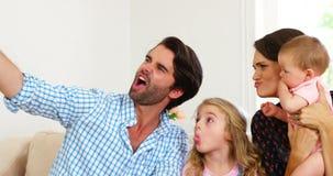 Familia linda que ríe y que toma una foto almacen de video