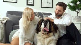 Familia linda que se relaja junto en el sofá con su perro en la manta en sala de estar en casa Retrato de la familia con a metrajes