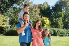 Familia linda que sonríe en la cámara en el parque Foto de archivo libre de regalías
