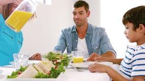 Familia linda que tiene el almuerzo y la madre que vierten el zumo de naranja metrajes