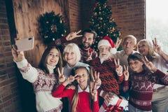 Familia llena alegre que muestra la v-muestra del festure de dos fingeres Gat de Noel imagen de archivo