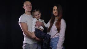 Familia llena feliz, padre que detiene a su hija, situación de la madre al lado de ellos almacen de video