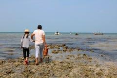 Familia local de los pescadores con el barco en la playa Imagen de archivo libre de regalías