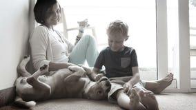 Familia, madre e hijo felices en piso con el perro amistoso del beagle almacen de metraje de vídeo