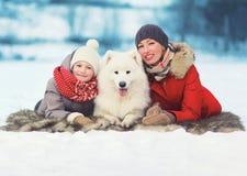 Familia, madre feliz e hijo sonrientes caminando con el perro blanco del samoyedo en invierno Imagen de archivo libre de regalías