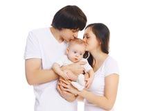 Familia, madre feliz y padre jovenes besando al bebé en blanco Imagen de archivo