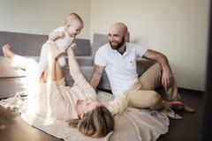 Familia, madre feliz y padre jugando con una pequeña hija en casa Copie el espacio Mujer que miente en piso y sostenerse foto de archivo libre de regalías