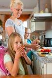 Familia - madre que hace el desayuno para la escuela Foto de archivo