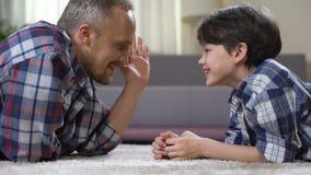 Familia masculina que juega en el piso en casa, divirtiéndose junto, ocio del fin de semana almacen de video