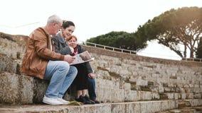 Familia mayor caucásica feliz con la hija joven que se sienta y que habla en ruinas del anfiteatro en Ostia, Italia con un mapa almacen de video