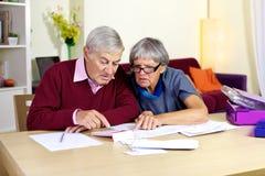 Familia mayor que intenta hacer cuentas financieras en cuentas Imágenes de archivo libres de regalías