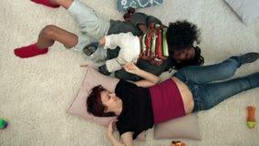 Familia mezclada feliz con el niño que miente en el piso metrajes