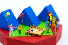 Familia miniatura usando como día internacional del fondo de concepto de familias imagen de archivo