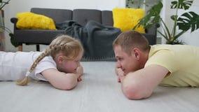 Familia moderna feliz El papá y su pequeña hija son de mentira y de mirada de uno a en el piso en la sala de estar metrajes